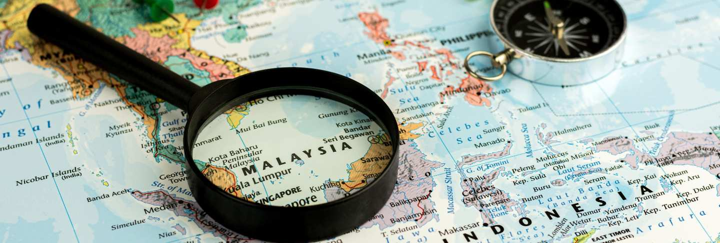 magnifying glass on the world map selective focus at malaysia map. - economic and business concept. Premium Photo